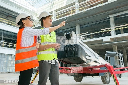 1129095769 istock photo Woman architect and man builder at a construction site. Building, development, teamwork and people concept 1028669230