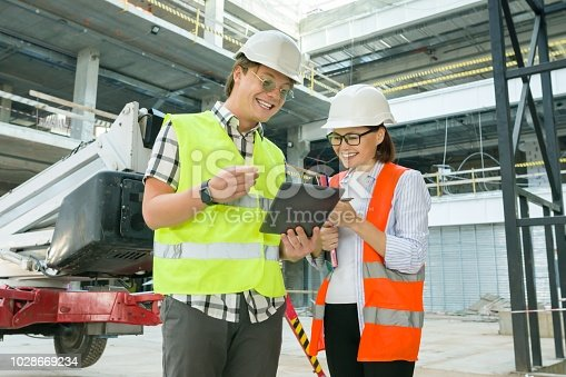 1129095769 istock photo Woman architect and man builder at a construction site. Building, development, teamwork and people concept 1028669234