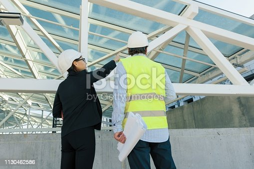 1129095769 istock photo Woman architect and man builder at construction site, back view. Building, development, teamwork and people concept 1130462586