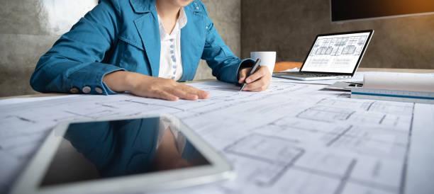 mujer diseñadora de arquitectos dibujando en planos. - arquitecta fotografías e imágenes de stock