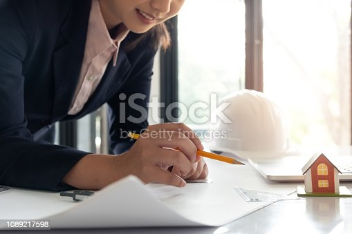 istock Woman architect drawing on blueprint for house planning, architectural concept 1089217598