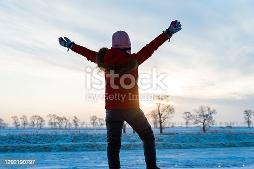 Woman arms outstretched by the lakeside in winter.