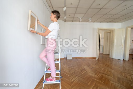 508897972 istock photo Woman arranging artwork on the wall 1041647506