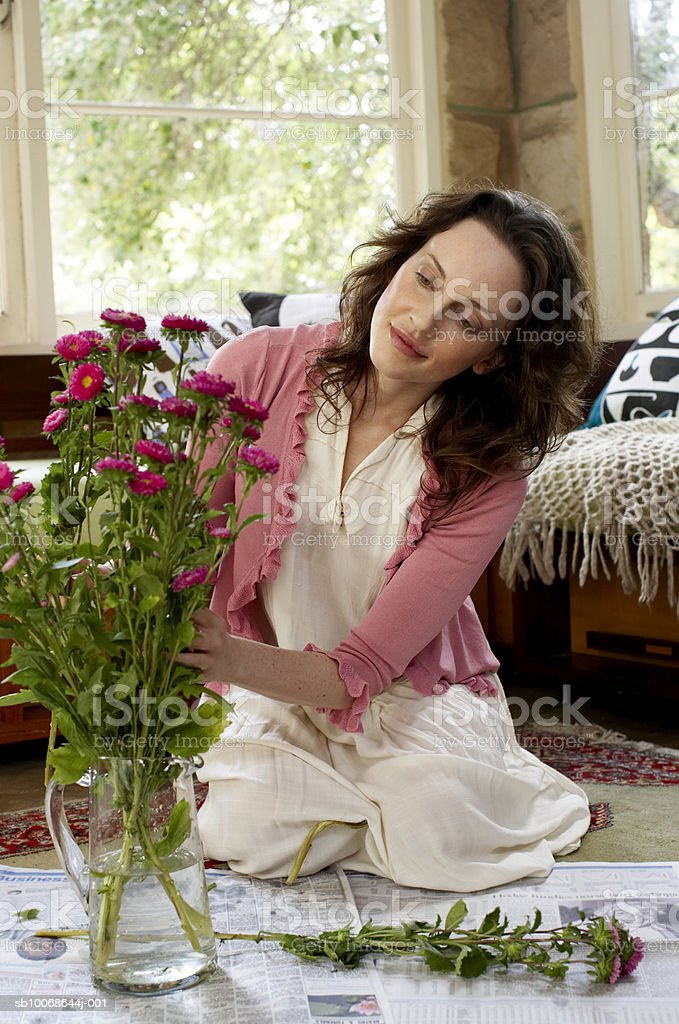 Woman arranging flowers in vase, smiling royalty-free stock photo