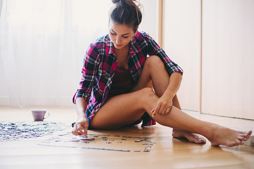 istock Woman arranging jigsaw puzzle at home 1158882118