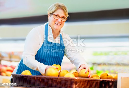 istock Woman arranging pears at grocery store 637925688