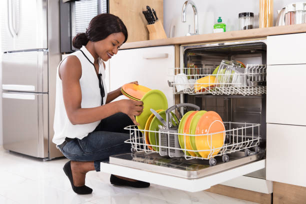 Woman Arranging Plates In Dishwasher Smiling Young African Woman Arranging Plates In Dishwasher dishwasher stock pictures, royalty-free photos & images