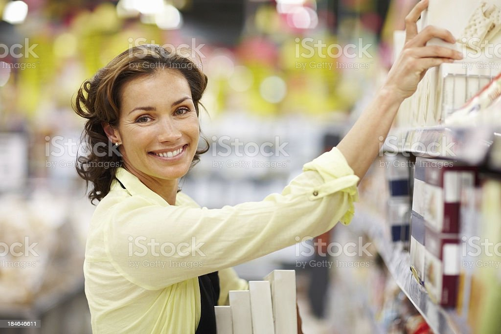 Woman arranging products on shelf royalty-free stock photo