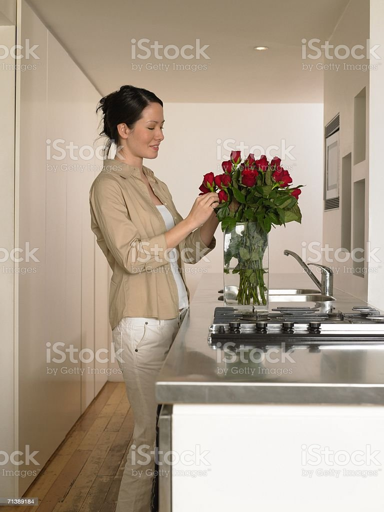 Woman arranging roses in vase royalty-free stock photo