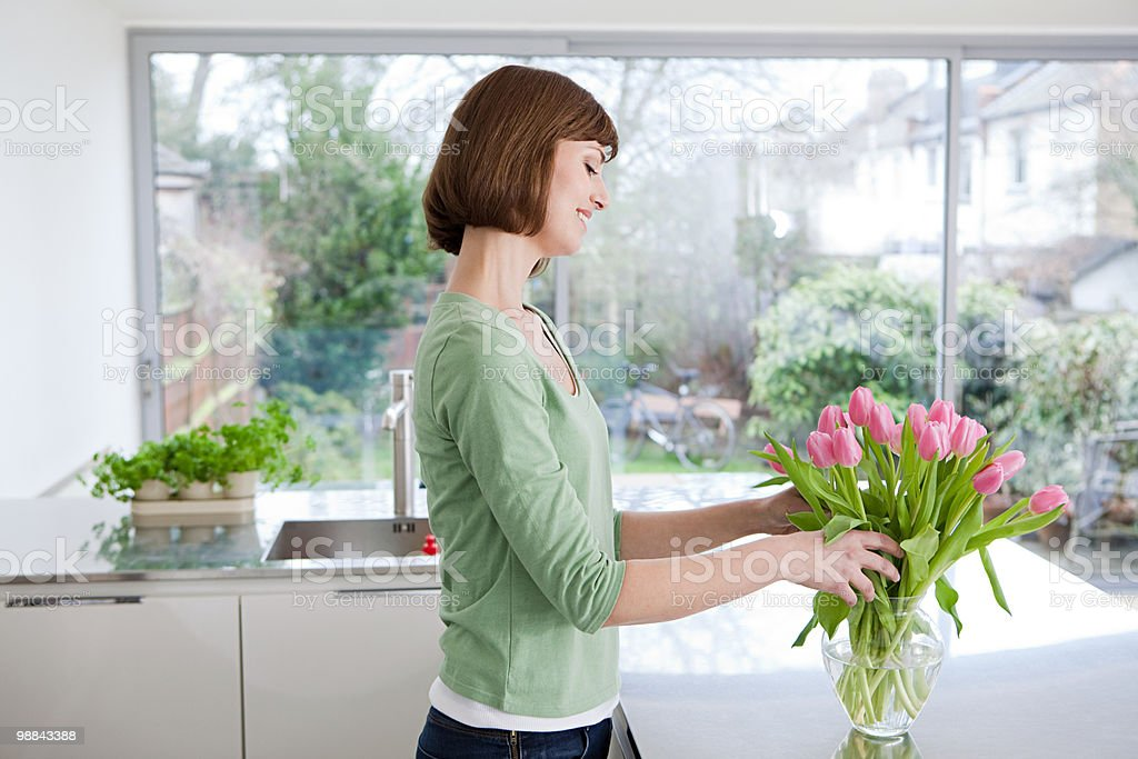 Woman arranging tulips in vase stock photo