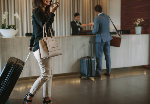 Woman arriving at hotel lobby with suitcase stock photo