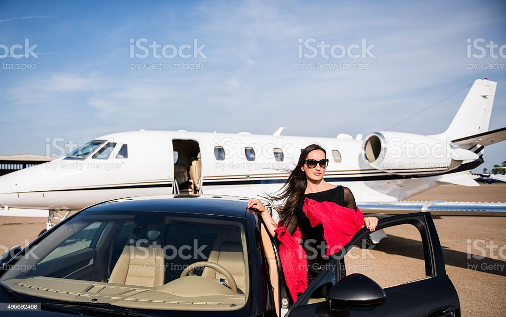 Woman arriving by car on airport track stock photo