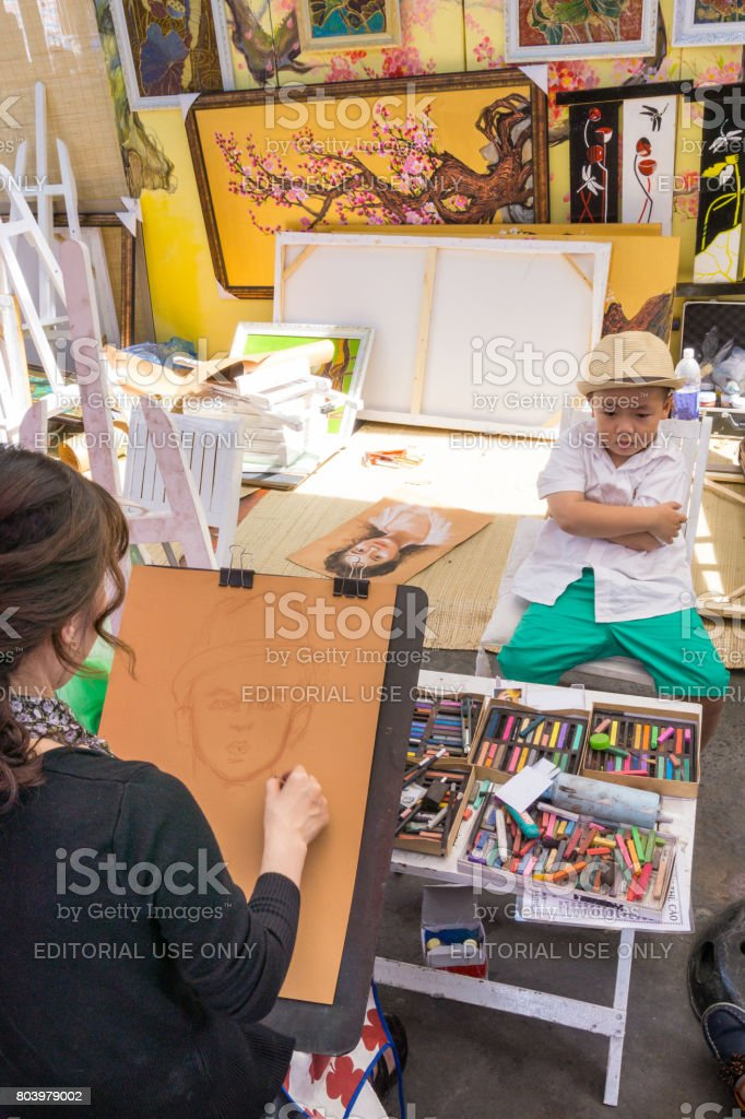 A woman artist drawing a boy стоковое фото