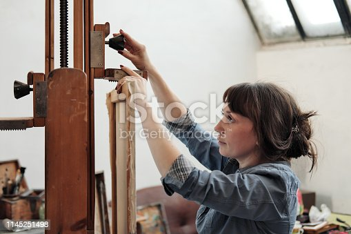 istock Woman artist fastens a canvas on a large wooden easel. 1145251498