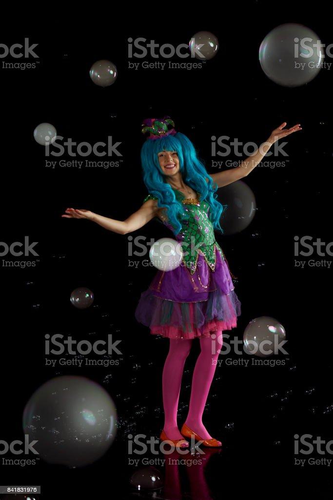 Woman artist fiddle with many soap bubble. Soap bubble show in black studio. stock photo