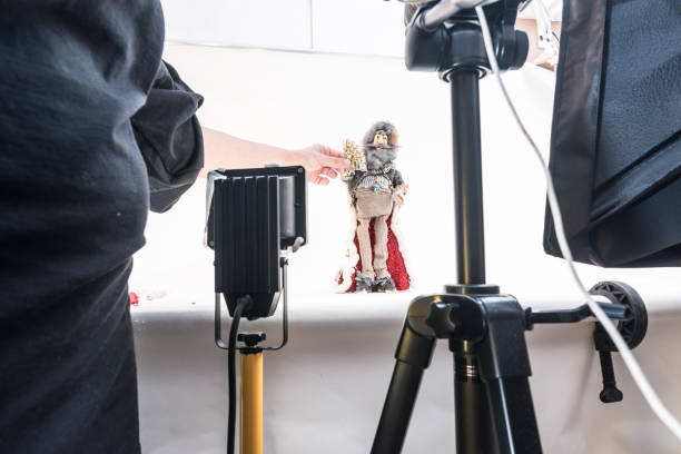 woman artist in home studio creating stop motion animated video, using digital camera to capture puppets frame by frame to produce the appearance of movement - stop motion stock photos and pictures