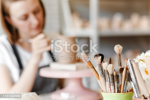 istock A woman artist in working apron smiles and paints a clay pottery among brushes and other tools in the modern workshop 1147402050