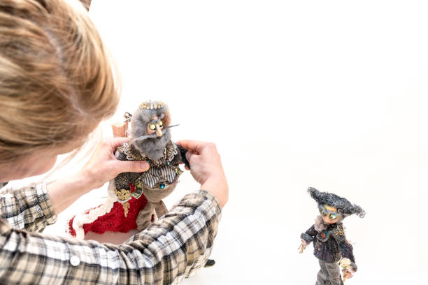 woman artist make stop motion animated video film, frame by frame, using old toys and dresses to adapted in new characters - stop motion stock photos and pictures