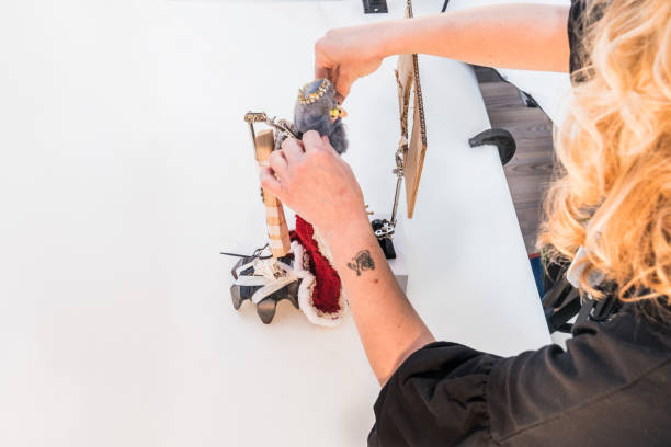 woman artist making stop motion animation movie by capturing frame by frame to creat the illusion of moving objects - stop motion stock photos and pictures