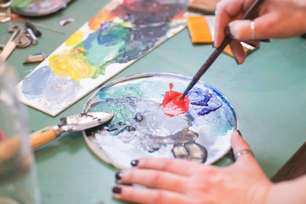 mujer artista mezclando colores en la paleta - foto de stock