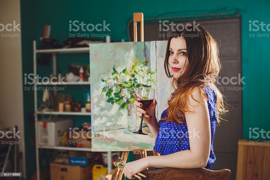 Woman artist painting a picture in a studio stock photo