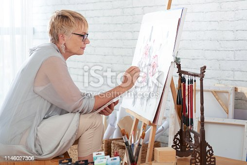 Mature woman sitting in art studio in front of easel and painting a picture with paints