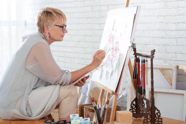 woman artist painting a picture - malarstwo zdjęcia i obrazy z banku zdjęć