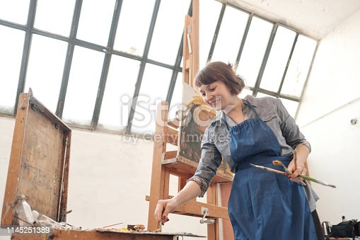937313030 istock photo Woman artist paints a picture on canvas. Bright art studio with a large window. Easels and canvases. 1145251389