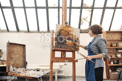 istock Woman artist paints a picture on canvas. Bright art studio with a large window. Easels and canvases. 1145251414