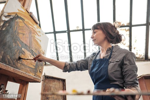 istock Woman artist paints a picture on canvas. Bright art studio with a large window. Easels and canvases. 1145251417