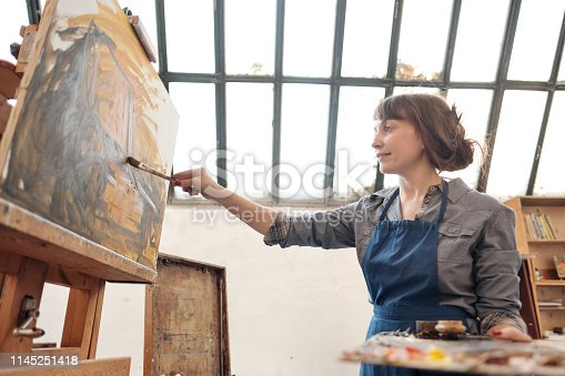 istock Woman artist paints a picture on canvas. Bright art studio with a large window. Easels and canvases. 1145251418