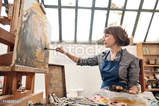 istock Woman artist paints a picture on canvas. Bright art studio with a large window. Easels and canvases. 1145251471