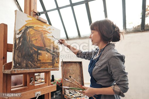 937313030 istock photo Woman artist paints a picture on canvas. Bright art studio with a large window. Easels and canvases. 1145251477