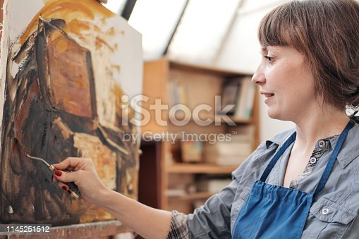 937313030 istock photo Woman artist paints a picture on canvas. Bright art studio with a large window. Easels and canvases. 1145251512