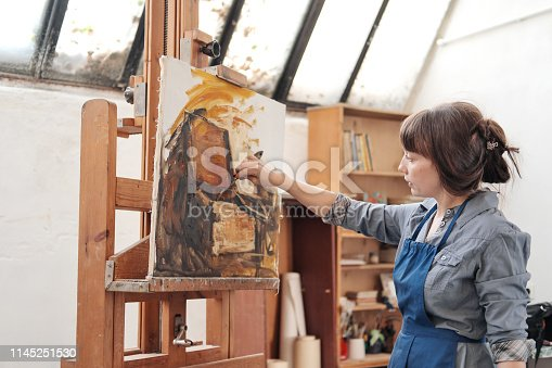 937313030 istock photo Woman artist paints a picture on canvas. Bright art studio with a large window. Easels and canvases. 1145251530