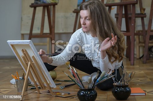 469937444 istock photo Woman artist sits on the floor in an art studio and paints an oil painting on canvas. 1211826855