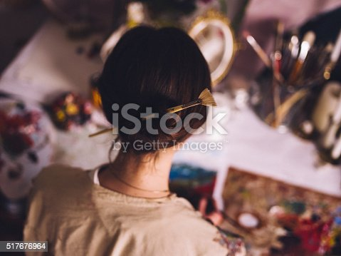 High angle view of a woman artist with her hair sept up with a paintbrush holding it while she working in her studio at her desk painting