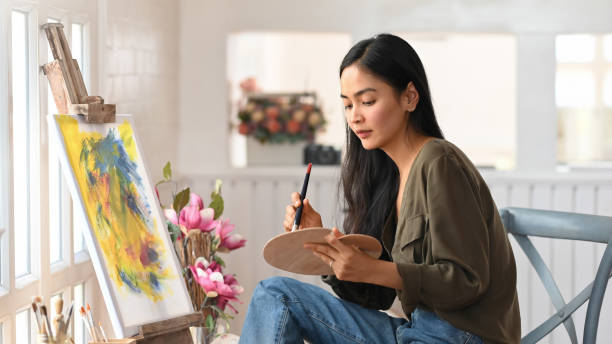 Woman Artist Works on Abstract acrylic painting in the art studio. stock photo