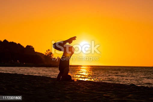 Woman doing yoga asana on the beach during sunset, relaxed, calm and serene