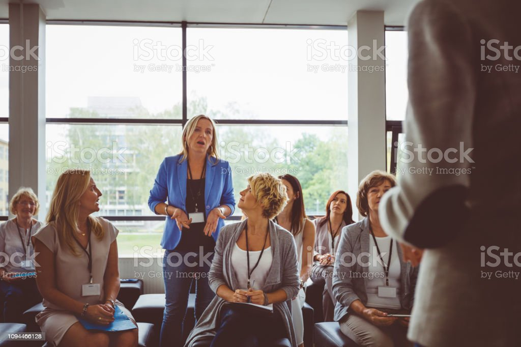Woman asking question during seminar Businesswoman standing in audience and asking a question to the speaker during seminar Adult Stock Photo