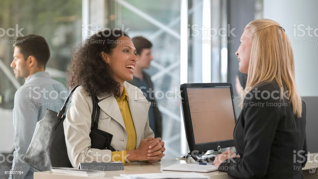 Woman asking rental agent for rental car type and female agent helping her stock photo