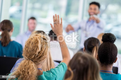 istock Woman asks question during healthcare seminar 864410940