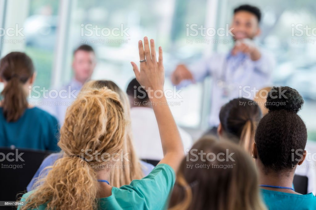 Woman asks question during healthcare seminar stock photo