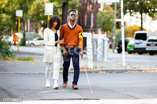 istock Woman Assisting Blind Man On Street 1177796470