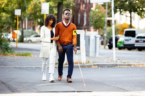 istock Woman Assisting Blind Man On Street 1177796470