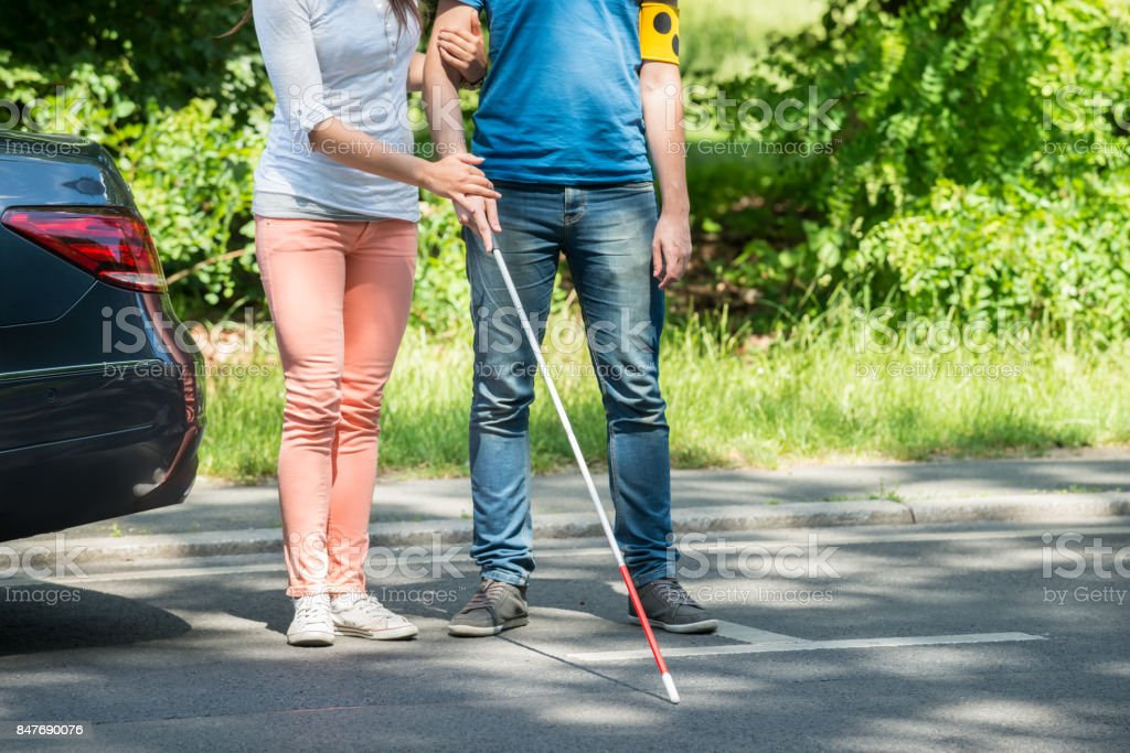 Woman Assisting Blind Man On Street stock photo