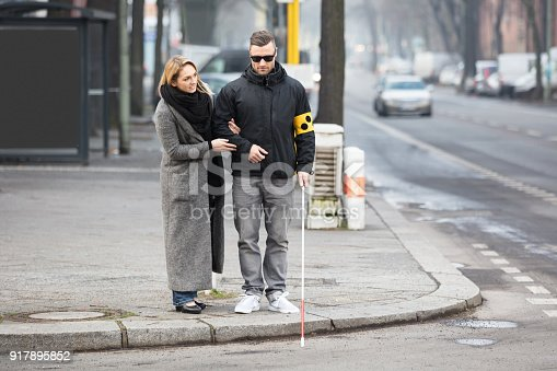 istock Woman Assisting Blind Man On Street 917895852