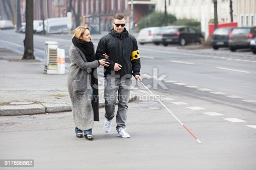 istock Woman Assisting Blind Man On Street 917895862