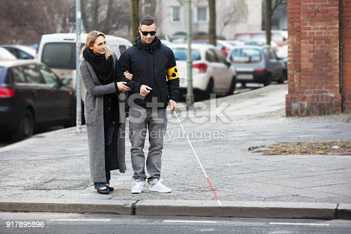 istock Woman Assisting Blind Man On Street 917895896