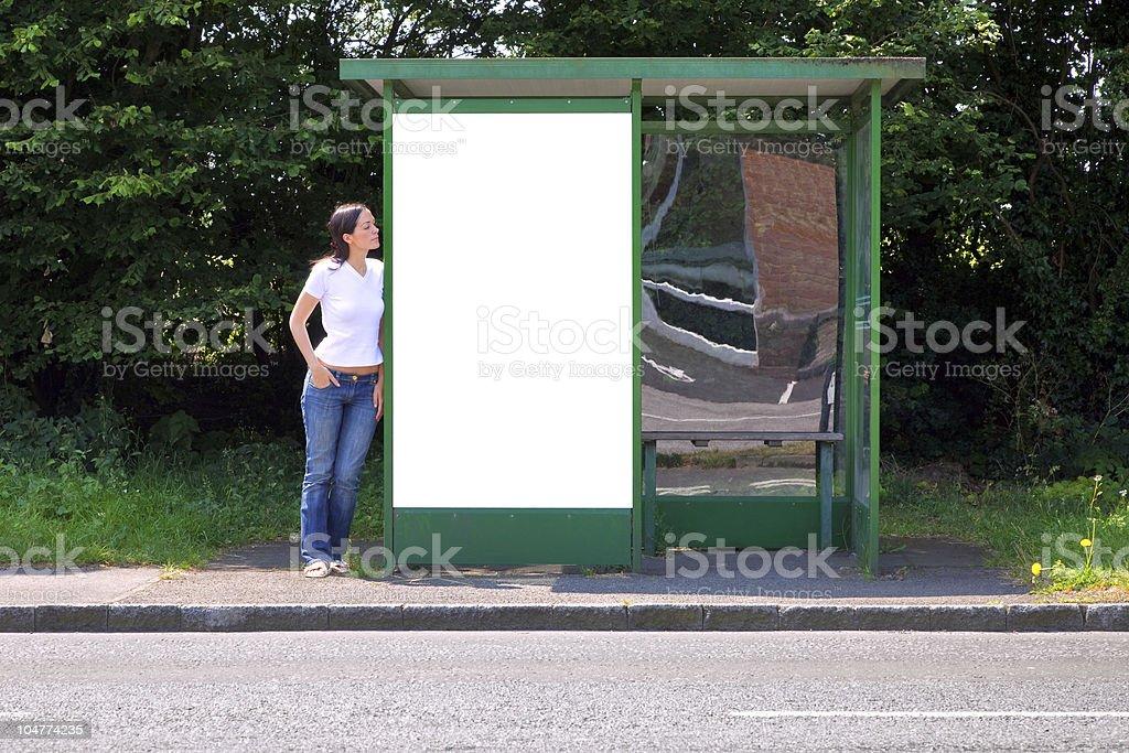 Woman at a bus stop blank billboard stock photo